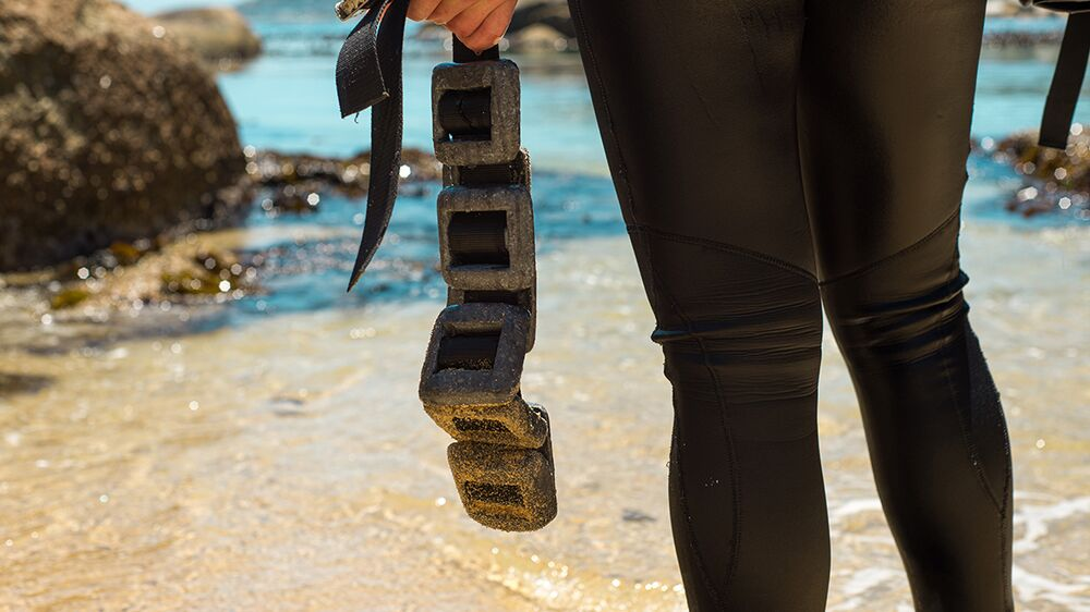 Diver standing on beach holds a loaded weight belt