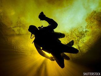 Scuba diver silhouetted in Florida spring